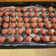 Råa köttbullar som ligger på en ugnsplåt och som ska in i ugnen, 225 grader.