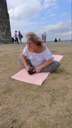 Ann Ahlgren utför Reiki Yoga på Glastonbury Tor, UK