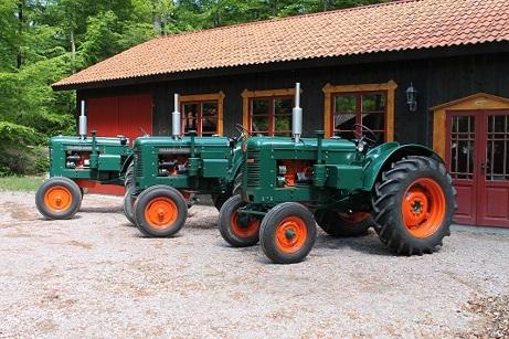 Tre renoverade traktorer framför traktormuseet
