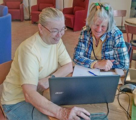Två glada damer som uppskattar Seniornet.