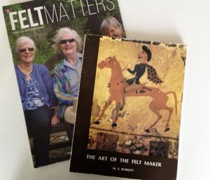 Mary Burkett ihop med Sheila Smith (vänster) och Inge Evers (höger) på omslaget till FeltMatters i samband med Marys 90-årsdag.  Framför ser du omslaget till hennes bok The Art of Felt Makers.