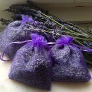 Tre lila organzapåsar fyllda med doftande lavendelblommor.