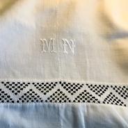 Ett fint handvävt linnelakan med mittsöm och virkad spets.