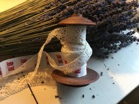 Spetsar, monogramband upprullade på antik bobinrulle. - En bobinrulle med vackra spetsar och namnband