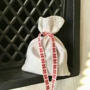 En fin handsydd lavendelpåse med spets. Äldre band i rött och vitt.