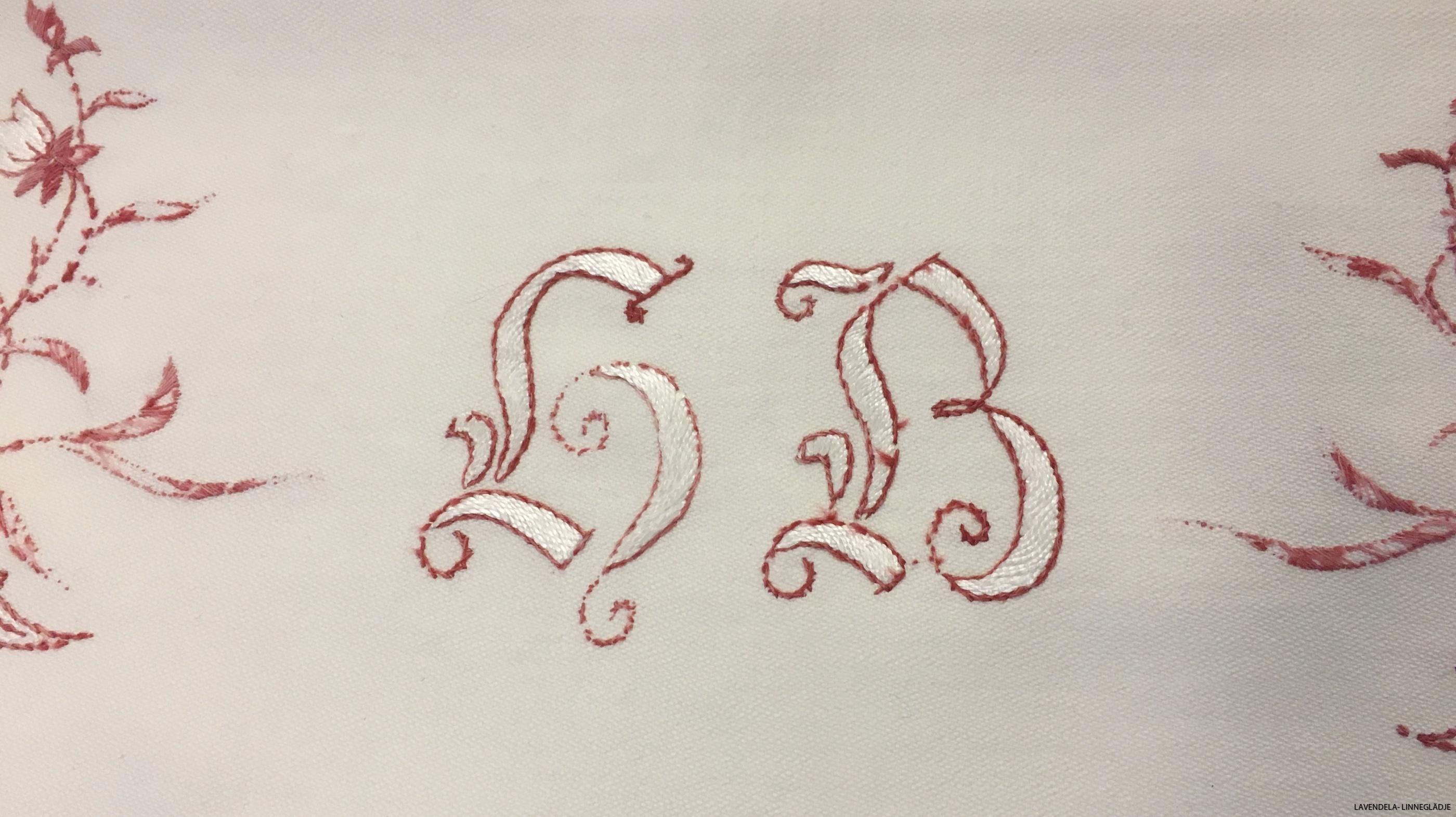 Monogram i snirkliga bokstäver.