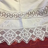 Ett vackert handvävt linnelakan med vitbroderier och spetsar.