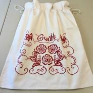 En mycket fin tvättpåse i bomull och handbroderad i rött.