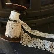 En antik bobinrulle med en handknypplad spets, 320 cm och en smalare tyllspets.