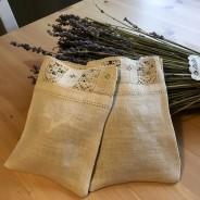 En handsydd lavendelpåse i linne med en handknypplad spets.
