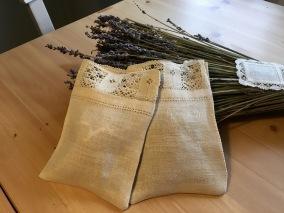 En handsydd lavendelpåse i linne med en handknypplad spets. - En handsydd lavendelpåse.