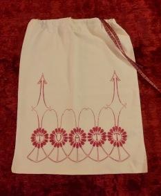 En äldre tvättpåse, handbroderad i rött och vitt. - En välbroderad tvättpåse.