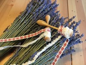 Två knyppelpinnar med upprullade handgjorda spetsar och ett fint band. - Knyppelpinnar, spetsar och band
