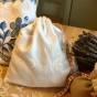 En handsydd lavendelpåse i ett vackert linnetyg m vitbroderi.