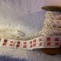En antik bobinrulle med spetsar och monogramband. - En antik bobinrulle