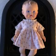 """En söt docka """"the sun rubber"""" klädd i en klänning."""