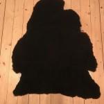 Nr: 18022. Finullsskinn, svart. Ekoberedning 35mm. 99x76cm. Mjukt och tjockt men med skada/jack vid halsen. Pris: 900kr