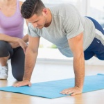 7889091-trainer-assisting-man-with-push-ups