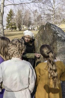 Lena Holmer, initiativtagare till Vikingamulle, visar barnen hur man läser runskrift. Foto: Peter Ullberg.