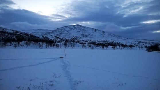En brunn är gjord i isen på sjön utanför fjällstugan Lunndörren.