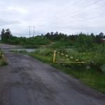 En öppen vägbom som leder mot bron.
