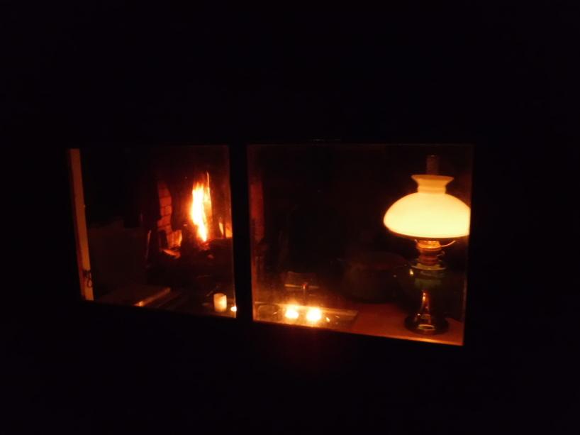 Höstkväll i Arvidssonstugan, med fotogenlampa, stearinljus och eld i den öppna spisen.