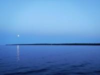 Klockan har passerat midnatt och månen vakar över mig och min båt.