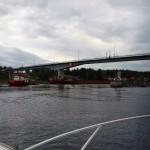 Under bron kommer en båt som bogserar en lång pråm.