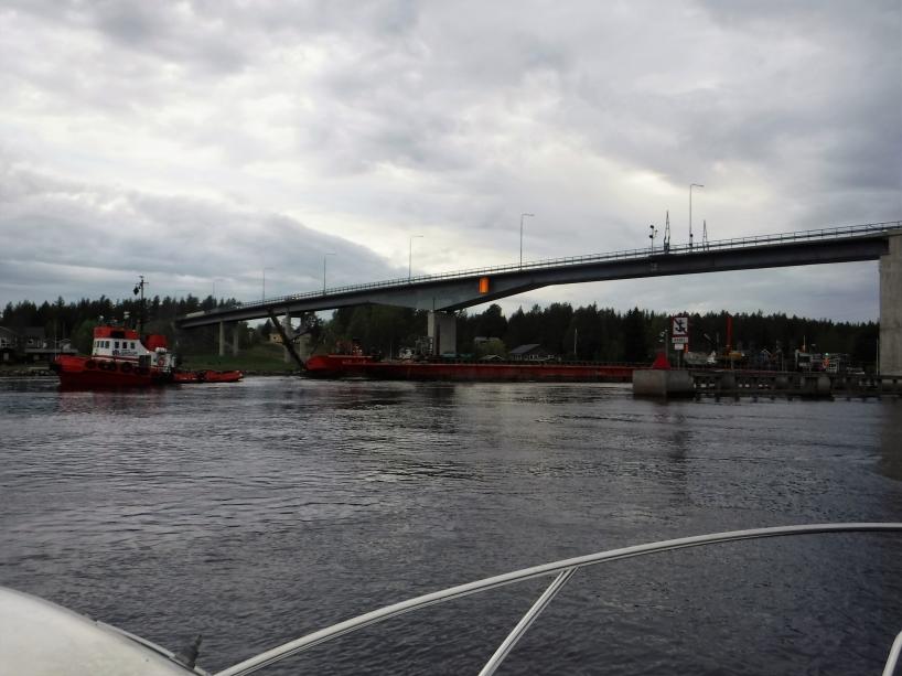 På väg in under Pitsundsbron, där det även kommer en båt som bogserar en lång pråm.