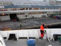 En besättningsmedlem gör sig beredd att kast en liten tamp (som är fäst i en större tamp) till en hamnarbetare i Sandnessjøen.
