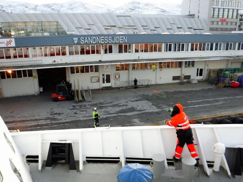En besättningsmedlem ur MS Vesterålens besättning kastar en liten tamp (som är fäst i en större tamp) till hamnpersonalen på land som ska hjälpa till att förtöja MS Vesterålen i Sandnessjøen.
