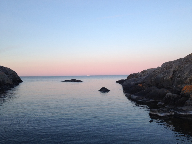 Långt utanför Österhamns utlopp från Landsort, så skymtar man siluetterna av ett fartyg.
