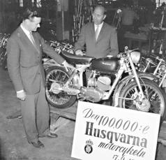 Två mycket nöjda herrar vid den 100.000:e Husqvarna-motorcykeln som levererades den 17 juni 1955. Produktionschefen Gunnar Ferbe och försäljningsdirektören Harald Carlström (bakom motorcykeln) diskuterar leveranser.