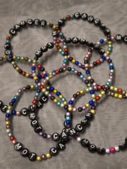 Armband, små pärlor blandat svarta bokstäver