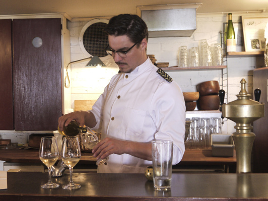 Jonas serverar ett av sina vita naturviner från den välfyllda vinkällaren