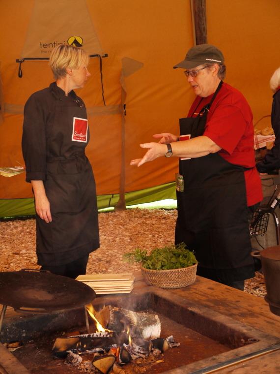 Marita från Ekebacken får en lektion i matlagning över öppen eld av Lisbeth från Stenshult Mellangård.