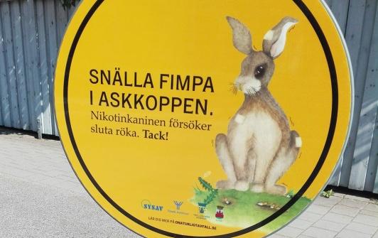 """Fin skylt med kanin och texten """"Snälla fimpa i askkoppen. Nikotinkaninen försöker sluta röka. Tack!"""""""