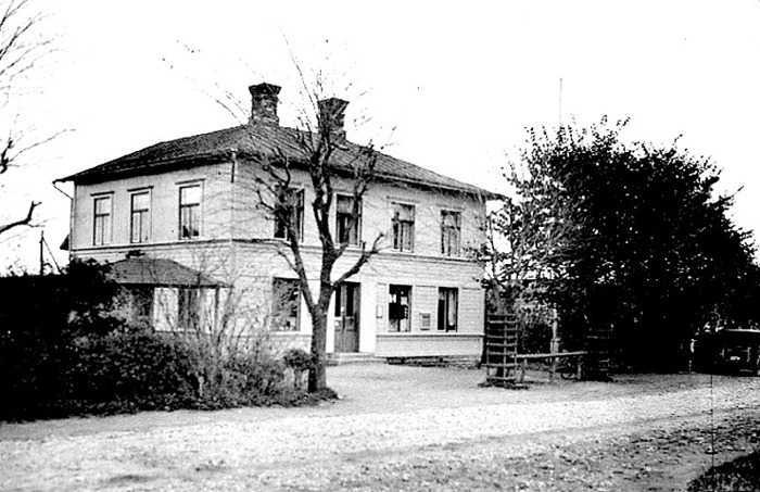 """A. 5 (1) Anton Larsson diversehandel i Varnhem år 1925. Skövde-vägen med en tankande bil och häststången för angörande av hästar framför affären på samma bild! Det sysn en skymt av bensinpumpen - """"Pratts bensin"""". Tll vänster fanns en kiosk. Vid denna tid var det vanligt att åka efter häst tilll affären. Hästarna bands då vid stången som syns mellan träden. En sådan stång fanns vid de flesta affärer på landsbygden. Den kallades ofta för """"lunsastånga"""" eftersom ortens ynglingar samlades där om kvällarna. Huset omändrades 1982 till bostadshus, sedan n y affärslokal tidigare byggts öster om den gamla. Flaggstången har också komit upp! Foto T. Hartman. Insatt av Kent Friman, 2014-02-14. Läs mer på www.saj-banan.se!"""
