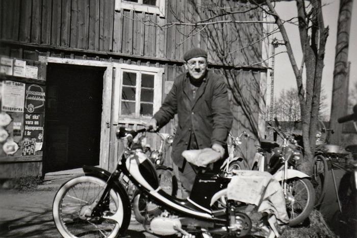 A. 35 (4) Endast digital bild! Knut Ohlsson vid sin Reparationsverkstad för cyklar, mopeder och allt annat som man önskade lagat. Den var under 1950-60-talet förlagd till uthusbyggnaden bakom (norr om) Manufakturaffären Gärdhem. SAJs infartssemafor till Varnhems station kan ses på bilden till höger om byggnaden, där spåret går på en någon meter upphöjd terrassering förbi Gärhem ut över landsvägen mellan Skara och Skövde. På affischen kan man se namnet Rolf Tibblin sammankopplat med Husqvarna. Tibblin var född 7 maj 1937 i Stockholm och blev 1962 och 1963 världsmästare i motocross 500 cc, båda gångerna på märket Husqvarna. Bilden är alltså troligen från en bit in på 1960-talet. (Bild från sonsonen Jan Ohlson, 2013). Insatt av Kent Friman.2014-02-18. läs mer på www.saj-banan.se!