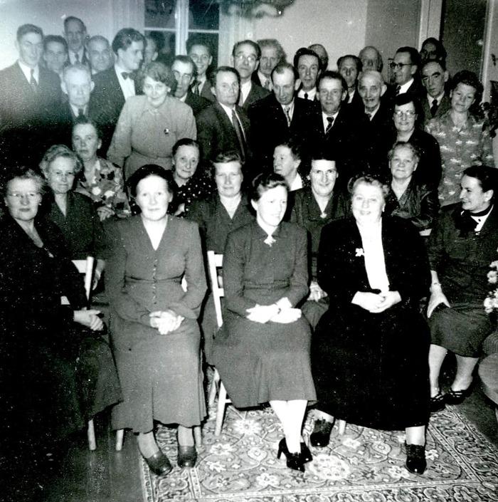 """A. 35 Endast digital bild. Fest i Runhem i slutet på 1930-talet med många Varnhemsbor kring """"Meli"""" i svart till höger längst fram i bild. """"Meli"""" var alltså Emelia Ohlsson, gift med Knut Ohlsson, som kikar fram i mitten bakifrån med glasögon. De båda ägde och drev Runhem som Kafé och verkstad, mm. Inga-Britt Lidbom fick arbeta hos dem från 1936 och sitter på bilden till höger om Meli - dvs i mitten av den främre raden och av bilden. Man kan även se folkskollärare Håkan Gabrielssons fru, Elsa, som nummer två från vänster och bakom henne en ung Haraldsson från Simmesgården, senare kommunstyrelseordförande. Handlaren Gustaf Österlund står i profil med glasögon till höger i bild, som efterträtt Anton Larsson i Nydal 1936 vid dennes död.  (Bild från 'systern' till Inga-Britt, Irma Meyer, 92 år, Skövde 2014) Insatt av Kent Friman, 2014-08-12."""