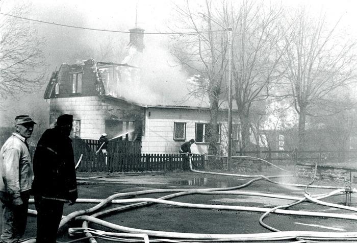 """I. 6 Runhem i ljusan låga (från öster) - helt övertänt i den hårda blåsten. Kiosken var sedan länge avvecklad och borta. Branden bekämpades av ett stort antal brandkårer från Skaraborg, men många hus gick inte att rädda! Verkstadsbyggnaden bakom huset flammar för fullt! Huset var utbyggt för att rymma matsal för eleverna i skolorna mitt över vägen och i församlingshemmet, så länge dessa var aktiva. Träden fick också sina brandskador. Kent Friman minns mötet med """"Edith på Caféet"""" en kort stund efter att huset var helt förlorat. Hon kom emot honom på landsvägen med en gräddkanna i handen som hon sträckte fram; """"Kent, detta är allt jag lyckades få med mig!! Allt är borta!"""". Det fanns dock en mindre del räddat av bohaget genom frivilliga insatser i sista stund, men det var inte mycket som fanns kvar efter lågornas rov! Insatt av Kent Friman, 2014-02-24. Läs mer på www.saj-banan.se!"""