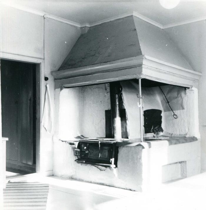 """A. 10 (3) Interiör från gamla köket på Hålltorp i Varnhem. Spisen togs bort vid ombyggnad 1954. I detta stora kök fanns förr, utom spisen, inget annat inrede än en diskbänk, en vedlår och ett vattenså. Ett stort skafferi eller handkammare i gången t.v. Vid fönsterväggen två utdragssoffor och ett långbord framför den ena. I köket arbetade en köksa och två pigor. Pigorna fick sova i utdragssofforna. Tre drängar fick också sina måltider här. Ägare i tidigare generationer intog sina måltider i ett rum innanför köket"""". Bild Västergötlands Museum - bildarkivet/bildnummer: A145127:60 Fotograf Nils Lann, Varnhem/Ljungstorp. Insatt av Kent Friman, 2014-02-17. Läs mer på www.ljungstorpshistoria.se!"""