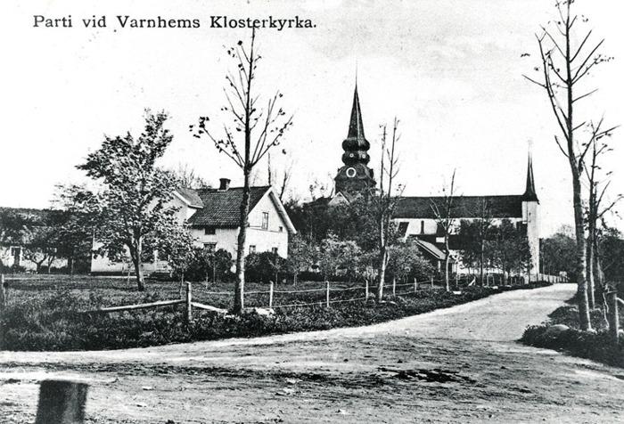 """B. 13 (1) Kyrkogatans infart 1910-1915 med Trädgården till vänster med """"gårdsstugan"""" i sin tur till vänster om boningshuset (flyttades över landsvägen under 1960-talet) och utanför bild ytterligare till vänster ligger mejeriet senare bageriet. Mellanskolan syns utmed kyrkogatan innanför staket till vänster och till höger skymtar svagt ett annat litet hus som då låg utmed Kyrkogatan ett stycke in från Folksskolan till höger (utanför bild). Insatt av Kent Friman, 2014-02-17. Läs mer på www.saj-banan.se!"""