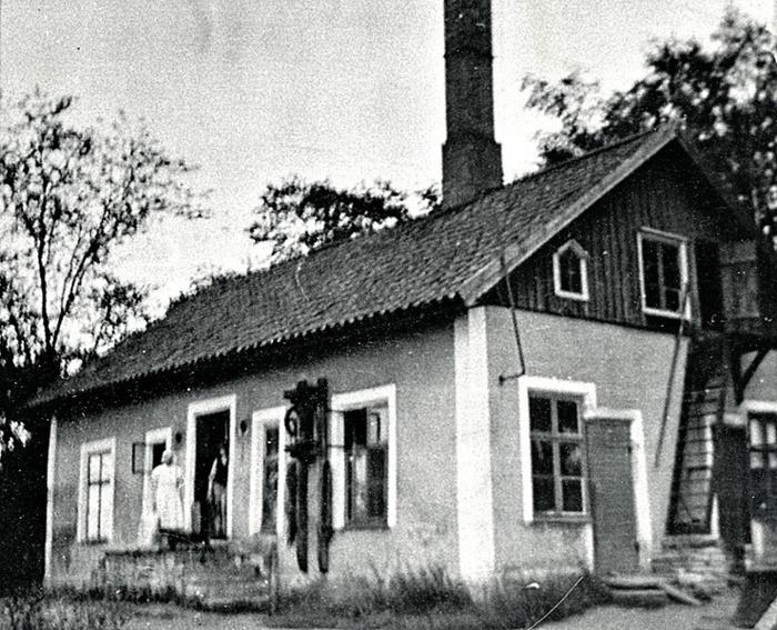 """A. 16 Trädgårdens mejer 1930-tal. Makarna Anna och Magnus Pettersson drev mejeriet. Inte långt från Klostergården finns denna byggnad på Trädgårdens östra husplatsmark som var uppförd som mejeri, men som under 1940-talet kom att bli bageri efter en brand. Bilden från mejeritidens 1930-tal. Byggnaden finns kvar ännu 2013 utmed muren nära kyrkans """"grovhanteringsupplag"""" och bod i norra delen av Kyrkparken mot gamla landsvägen Skara - Skövde. Insatt av Kent Friman, 2014-02-17. Läs mer på www.saj-banan.se!"""