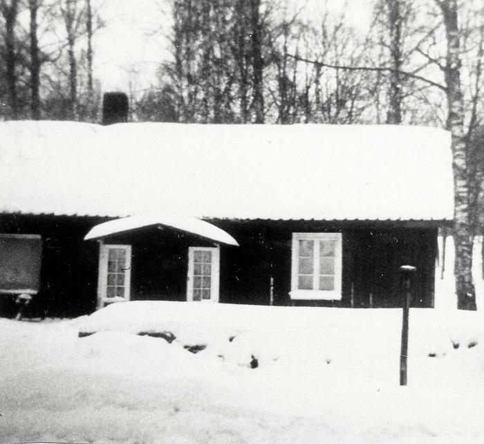 """A. 17 (2) Klockarejorden eller Klockarebohlet. Enligt bildtext """"Klockarejorden"""". På karta 1844 benämnt Klockarebohlet, dvs klockarens bostad. Den fanns belägen strax norr om kykrogårdsmuren för Varnhems kyrka och har bebotts av en rad klockare. Den inköptes redan 1876 av kyrkostämman av Sven Ferm för att bedriva en småskola. Under en tid på 1920-talet var den också Varnhems mellanskola, så att barnen slapp de långa färderna till Norra Lundby skola, med vilken man delat skolbyggnad och lärare tidigare. 1920 anställdes en biträdande lärare och huset blev alltså en slags mellanskola för klass 3 och 4 fram till 1929. Därefter var här träslöjd fram till 1951. Efter 1951 tog dåvarande kantor Lönnqvist huset i anspråk som kantorsbostad och bodde här tilslammans med fru Diana Appelqvist (under kriget konservfabrikägare) fram till 1967 innan huset revs svårt förfallet. Insatt av Kent Friman, 2014-02-17. Läs mer på www.saj-banan.se!"""