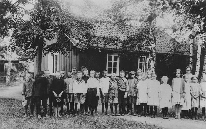 F. 15 Skolfoto från Varnhem omkring 1925, den s.k mellanskolan låg i kyrkeparken med Kyrkogatan i bakgrunden och det gamla stallet med offentliga toaletter (och skoltoalett). Insatt av kent Friman, 2014-02-24.
