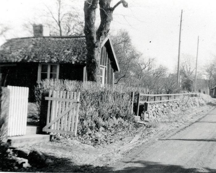 A. 20 (1) Jonssons skomarkastuga. Smedjebackens gamla stuga snett emot Fattigstugan och nära dagens korsning med Fermavägen. Det gamla huset stod fortfarande kvar under 1950-talet. Foto 1950-talet i riktning mot Skövdehållet. I kurvan längre fram till höger syns Backens ladugård. Fotograf Evert Gustavsson