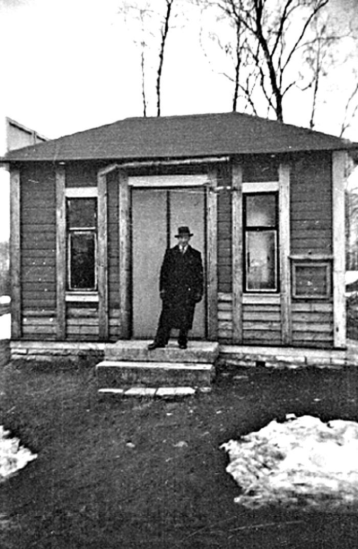 """A. 26 (1) Vid fototillfälle 1937 poserar sedan Karl Holmberg, Storekullen framför byggnaden som just det årtiondet hade förfallit en hel del. Karl Holmberg, Storekullen omkom i en el-olycka på Kyrkebo 1940. Bildtext ur arkivet: """"Ljungstorps anhalt. """"Väntsalen"""" vid Ljungstorps anhalt 1937. Byggnaden var ursprungligen tidningskiosk i Skövde kyrkpark och flyttades omkring 1914 (senast 1913 enl. tavlan) till Ljungstorp av disponent Grönvall och grosshandlare Högberg, vilken ägde ett par sommarställen i Ljungstorp. Byggnaden blev efter hand en träffpunkt för bygdens ungdom och kallades av folkhumorn för """"Lunsabingen"""". Smärre vandaliseringar och upprustningar avlöste varandra de sista åren före järnvägens nedläggning 1961."""" Foto Nils Lann (Text Västergötlands Museum - bildarkivet/bildnummer: A145127:6). Insatt av kent Friman, 2014-02-24. Läs mer på www.saj-banan.se! Klicka på bild för att se mindre bild!"""
