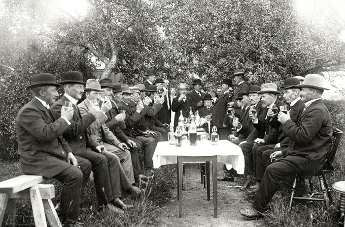 """F. 18 Ett svenskt """"Hipp, Hipp, Hurra"""" .""""Herrfest"""" med några upppassande damer i bakgrunden. Troligen 50-årskalas i """"Tomtasmen's"""" trädgård, där en stor del av bygdens bönder finns med! """"Tomtasmén"""" Anders Gustav Andersson född 5/8 1856. I så fall är bilden tagen 1906. """"Smen"""" själv i mitten med ljus hatt och pipskägg och med frun därbakom. Insatt av Kent Friman, 2014-03-03."""