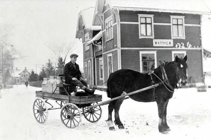"""C. 8 (1) Hålltorps mjölkskjuts vid Varnhems Järnvägsstation år 1926. Kusk Georg Lindström. Hålltorps mjölkskjuts år 1926 då Varnhems mejeri var igång. Kusken hette Georg Lindström. Skjutsen befinner sig utanför Varnhems post- och järnvägsstation, eftersom man också hämtade posten med samma skjuts. Lägg märke tilll granarna på led i Järnvägsparken innanför ett tätt staket. Lägg också märke till pump och vattenbalja för vattning av hästarna till höger. Mejerirörelsen upphörde på 1940-talet efter en brand. Ägare var då Magnus Pettersson och hans hustru Anna Pettersson, som var chef och mejerska. Den sist anställde hette Anders Pettersson. Rörelsen hade startats av Magnus Petterssons far """"Petter i Trädgår´n"""". Efter branden öppnade Anna Pettersson bageri i huset. Återförsäljning av mejeriprodukter ingick också till en del. Senare verksamheter i huset har varit mekanisk verkstad och antikvitetsrörelse. De närmast kända mejerierna i trakten har funnits på gårdarna Rökstorp och Ökull. (Text  från artikel i Varnhemsbygden av Arne """"Skultorparn"""" Andersson). Insatt av Kent Friman, 2014-02-26. Läs mer på www.saj-banan.se!"""